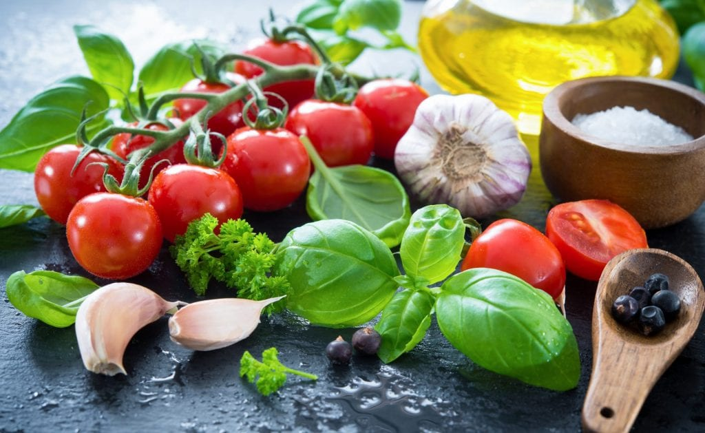 Foods on the mediterranean diet, including tomatoes, basil, garlic and olive oil